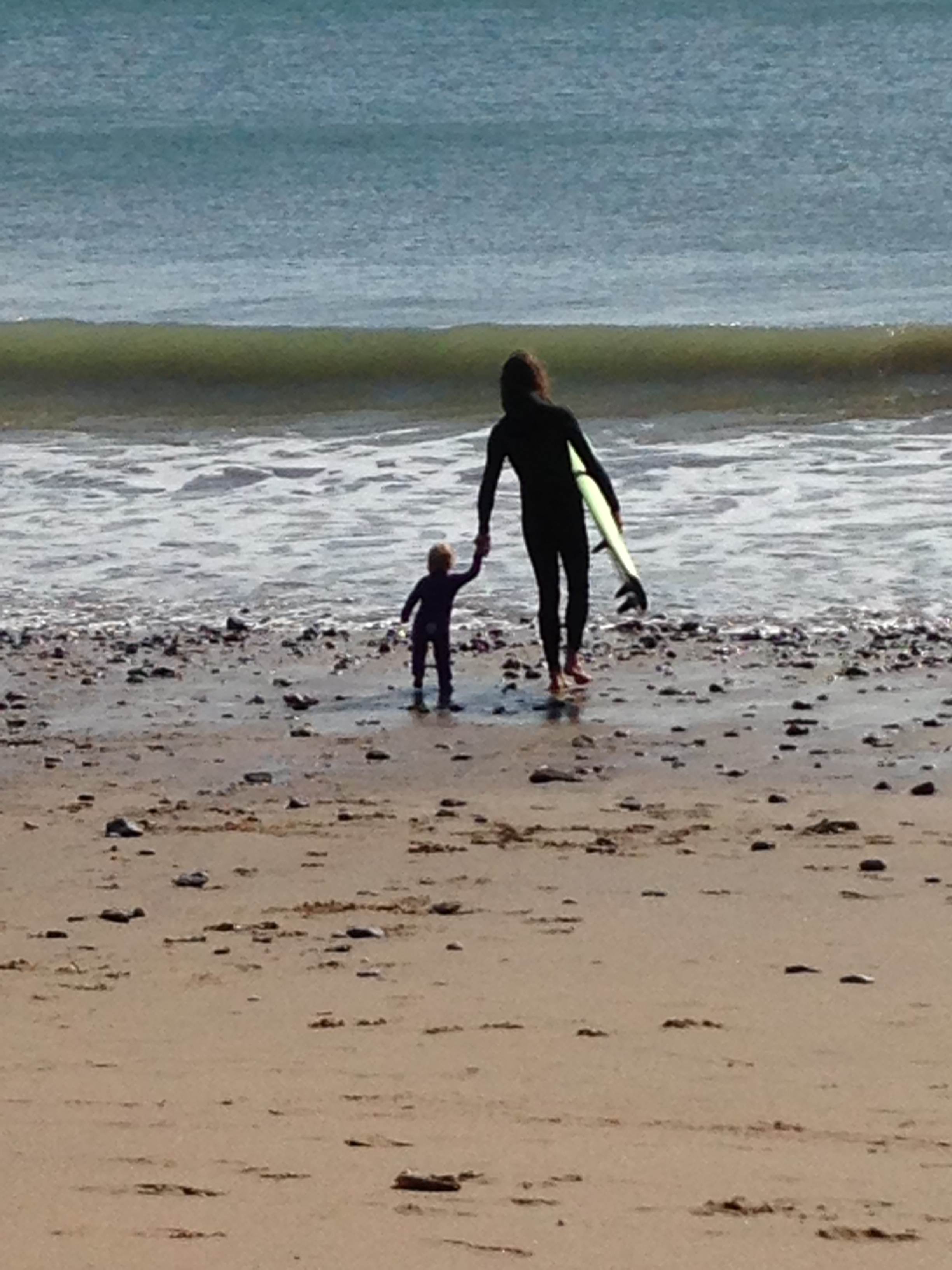 Little girl and her father walking towards the sea with surf board